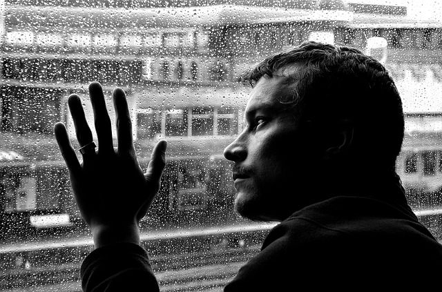 man beside raining window