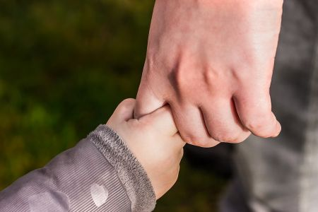 Child holding hands with adult