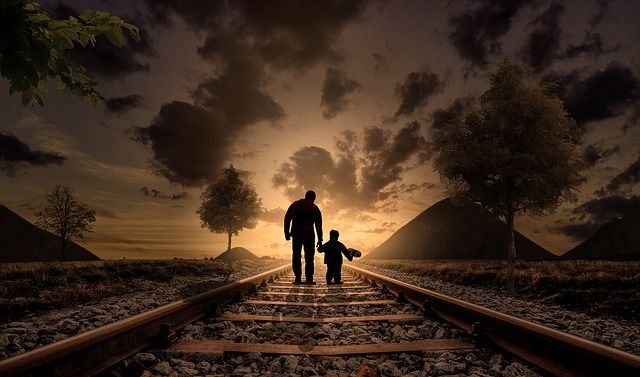 parent and child walk on train track
