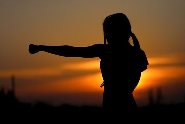 girl punching air at sunset