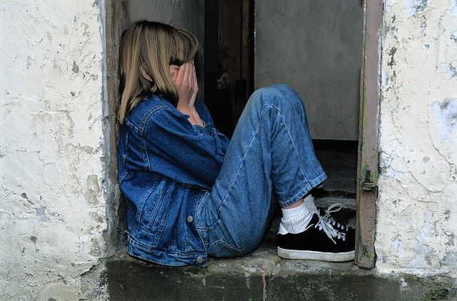 girl crying in doorway
