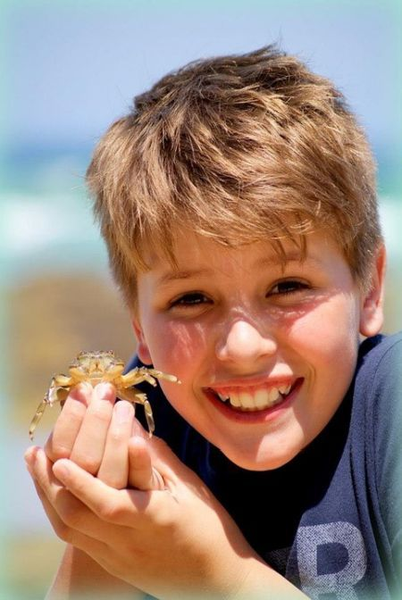 young boy holding crab