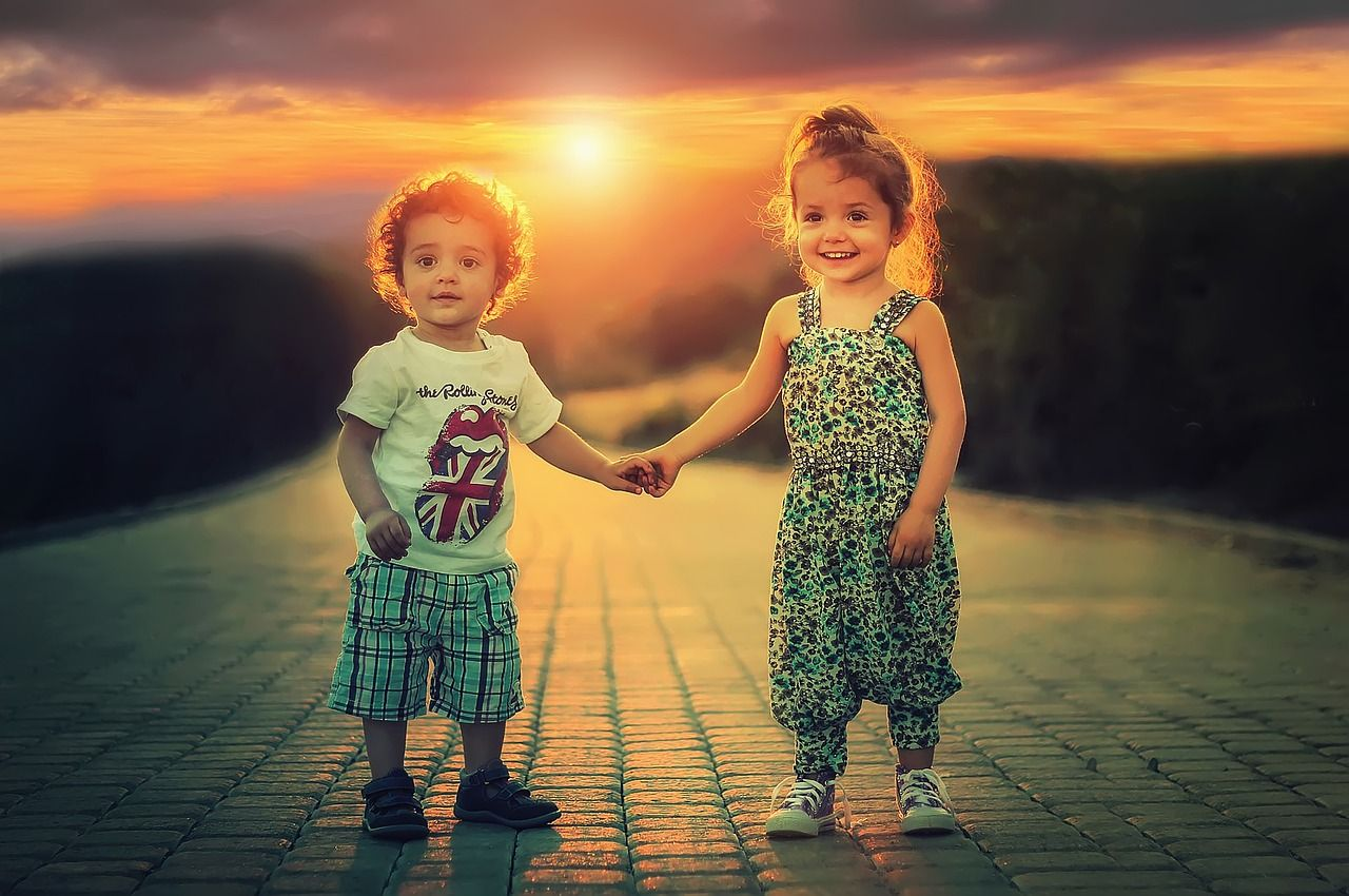 kids holding hand at sunset